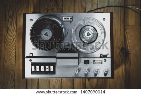 Vintage reel to reel tape recorder on a wooden floor #1407090014