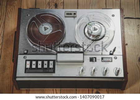 Vintage reel to reel tape recorder on a wooden floor #1407090017