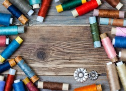 vintage reels of varicolored thread and old flower buttons on the textured surface of the ancient tailor's table