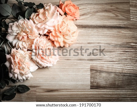 Vintage retro background with roses on wood. Romantic floral frame background.