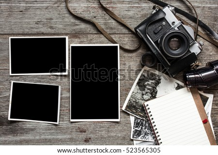 vintage retro camera on wood table background with blanks photos to placed your pictures and notebook.