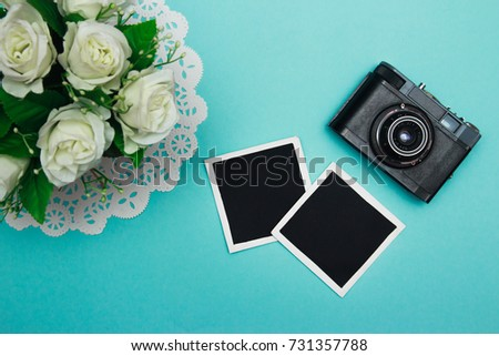 vintage retro camera on wooden table background with blanks photo to placed your pictures, bouquet of pink roses, gift boxes and heart made from film. valentines day background. top view
