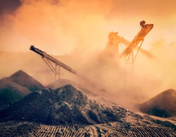 Vintage retro effect filtered hipster image of Industrial hell pollution background concept - crusher (stone crushing machine) at open pit mining processing plant for crushed stone sand and gravel