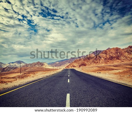 Vintage retro effect filtered hipster style travel image of Travel forward concept background - road in Himalayas with mountains and dramatic clouds. Ladakh, Jammu and Kashmir, India