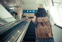 vintage retro film color photo. back view of female traveler carrying backpack and standing on electric escalator going to gate when she arrived airport.