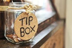 Vintage retro glass jar with hemp rope tie tip box tag and few coins inside on wood counter