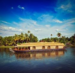 Vintage retro hipster style travel image of Kerala travel tourism background - houseboat on Kerala backwaters. Kerala, India
