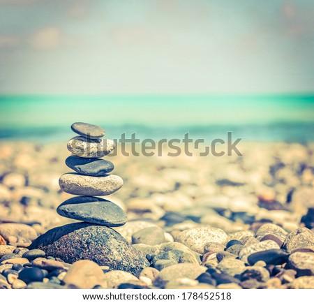 Vintage Retro Hipster Style Travel Image Of Zen Meditation Background - Balanced Stones Stack Close Up On Sea Beach