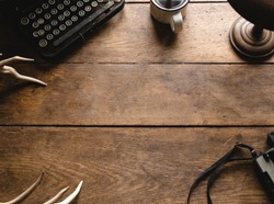 Vintage Retro Hipster Wooden Table Desk Background Texture Great for Display and Mockup with Old Camera, Black Typewriter, Bronze Lamp, White Deer Antlers and Coffee Mug with Black Coffee