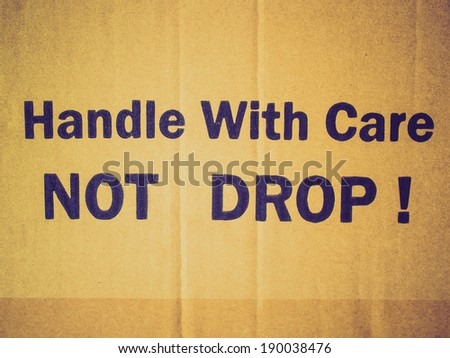Vintage retro looking Fragile Handle with Care Do not drop label on a corrugated cardboard box