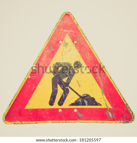 Vintage retro looking Road works sign for construction works in progress - isolated over white background