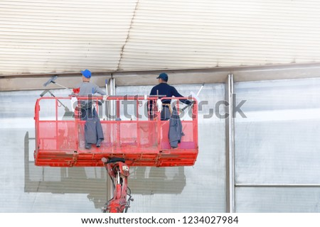 vintage retro men worker in crane gondola cleaning building facade window glass by using equipment tools to cleanup dirty surface close up exterior landscape aerial view people job activity background
