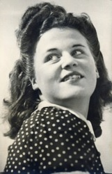 Vintage retro 1940s monochrome portrait of a young woman/girl wearing a polka dot dress and looking over her shoulder.