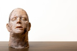 Vintage retro zombie mannequins head on wooden table and white background for copy space.