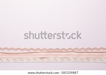 Vintage ribbon on soft pink and blue paper background.