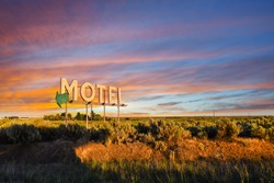 Vintage roadside highway Motel advertising sign seen through a colorful sunset in the American Desert of the Inland Northwest.