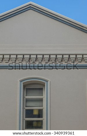 Vintage roof and exterior wall with arched window in tones of white, blue, and gray/grey, for use as an advertisement backdrop/message.