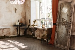 Vintage room with dirty walls, antique mirror, chair and big window