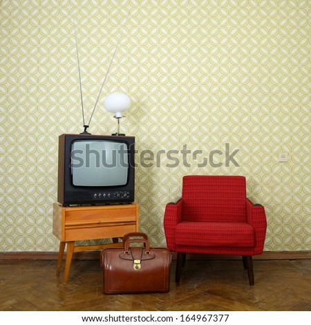 Vintage room with old fashioned armchair retro tv lamp and bag over obsolete wallpaper