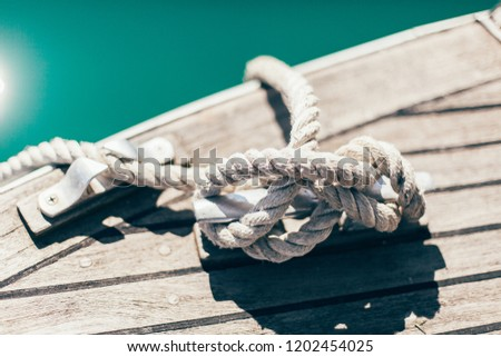 vintage rope from yacht on a wooden tick background with sunlights in sea