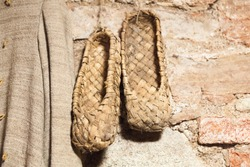 Vintage Russian bast shoes hang on brick wall. These shoes made from bast or fiber taken from the bark of trees such as linden or birch