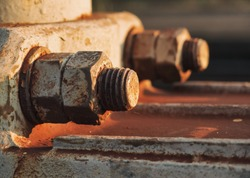 vintage rusted screws – bolts with nut in old railway. Corrosive grunge industrial construction close up. Iron corrosion. One bolt in focus and one out of focus. Two nuts on one stud.