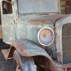 VINTAGE RUSTED UTE TRANSPORT WITH OLD HEADLIGHT AND DETERIORATED RUBBER TYRE, PALE GREEN RUST METAL