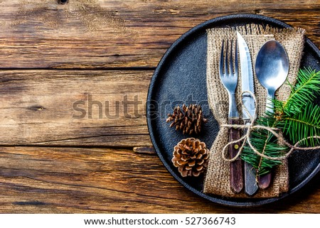 Vintage rustic cutlery set with country style napkin and Christmas decoration - fir tree brunch, cones on black iron plate on wooden background. Copy space, top view. Christmas menu background