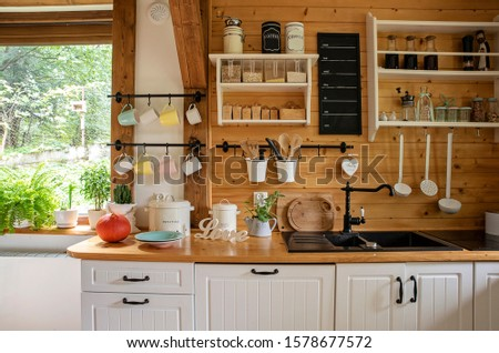Vintage rustic interior of kitchen with white furniture, wooden wall and rustical decor. Bright indoor with window. Cottage interior and style.