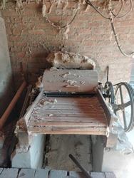 Vintage rusty and dusty cotton gin machine isolated on ground. cotton engine or cotton gin, that is used to separate the cotton fibers from the seedpods. Industrial equipment.