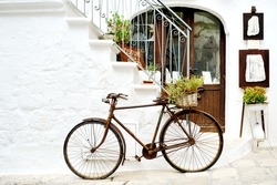 vintage rusty bicycle against a wall in white city Ostuni, Apulia, Italy - artistic picture italian style concept