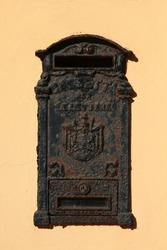 Vintage rusty black metal mailbox decorated with in relief coat of arms and text