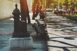 Vintage rusty brass or bronze water tap  standing on concrete base in park of Barcelona with several maroon benches near walking pathway of paving stone with shadows from trees