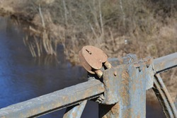 Vintage rusty iron railing on the bridge and rusty iron lock on the background of spring bare trees