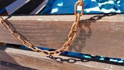 Vintage rusty metal chain hanging from wooden treasure chest. Fake pirate chest decoration details