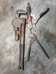 Vintage rusty metal iron adjustable plires wrench, water pump plires and water pump pipe wrench isolated on the floor. Set of Plumbing tools. Industrial equipment