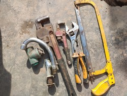 Vintage rusty metal iron pipe wrench, screw wrench, Pliers and hand hacksaw isolated on ground background. Plumbing tools, plumbing equipment