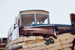 Vintage rusty old boat background. Damaged abandoned old-fashion boat, vintage ruined sailing ship wreck concept. Retired retro styled boat, outdated sea water vehicle. Shipwreck horizontal wallpaper