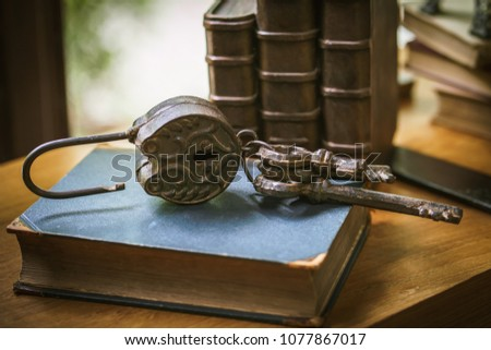 Vintage rusty padlock and old keys on the book with windows light .