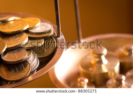 vintage scale wheights outweigh coins on an old balance