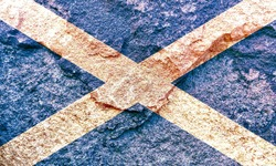 Vintage Scotland national flag icon pattern isolated on weathered solid rock wall background, abstract positive design faithful Scottish country politics society history concept texture wallpaper