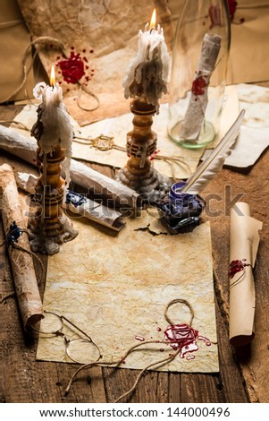 Vintage scrolls and candles are the old scribe\'s workplace