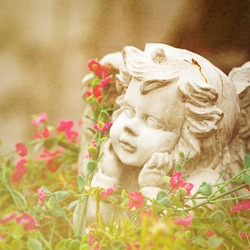 vintage sculpture of little angel among flowers