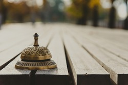 Vintage service bell on wooden surface, horizontal photo