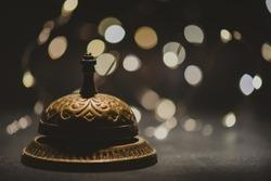 Vintage service bell with bokeh on dark backround, horizontal photo