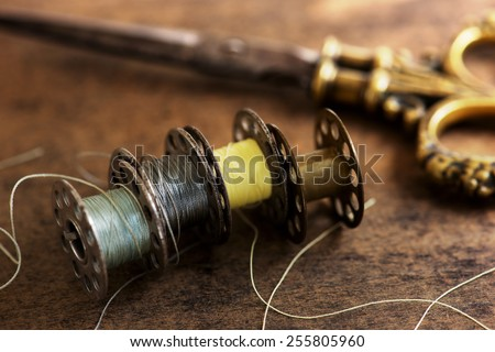 Vintage sewing machine bobbins with vintage gold ( brass ) scissors on a old grungy work table. Tailor\'s work table. textile or fine cloth making. Shallow depth of field.