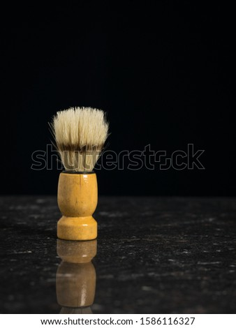 Vintage shaving brush for shaving on the stone table on a black background. Set for care of a man's face.