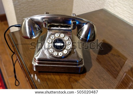 Vintage shiny metal rotary dial phone on wood table. #505020487