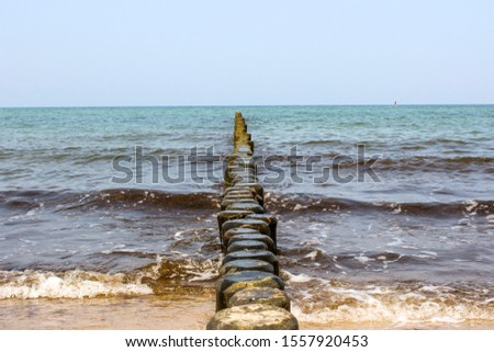 vintage shot of breakwaters made out of wooden stakes at the Baltic Sea in Germany/ wooden wave breakers at the colorful ocean, blue sky #1557920453