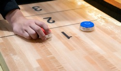Vintage shuffle board game with red and blue disc and hand holding red blue disc on wooden shuffle table. Shuffleboard table game with selective focus.